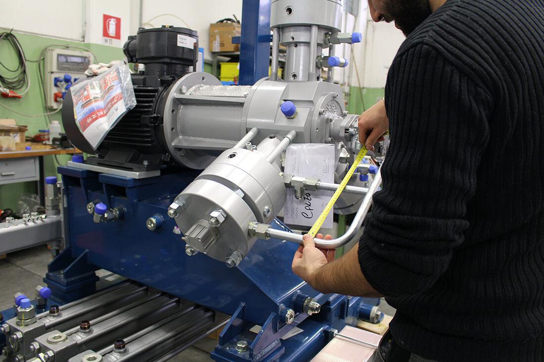 Foto di un operaio di tre quarti che prende le le misure di un macchinario di Calzoni Assemblaggi.