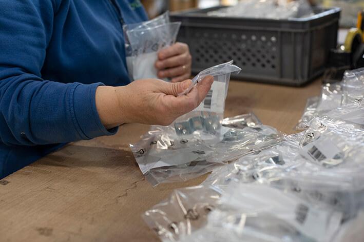 Dettagli delle mani di un'operaia che seleziona accessori industriali in bustine di plastica.