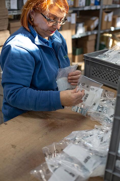 Foto di un'operaia a lavoro che seleziona accessori industriali in bustine di plastica.