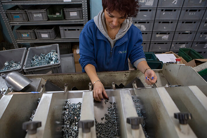 Foto di un'operaia al tavolo di lavoro con vari accessori industriali.