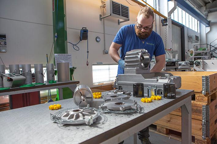 Foto di un operaio al lavoro con elementi di assemblaggio per l'elettromeccanica.