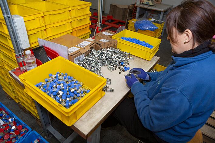 Foto di un'impiegata di Calzoni Assemblaggi a lavoro con alcuni accessori industriali.