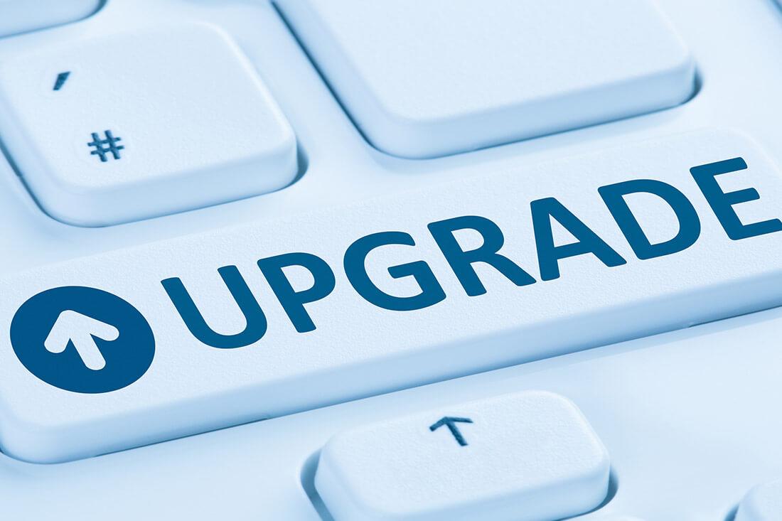 """Dettaglio di una tastiera di computer con al centro un tasto con la scritta """"upgrade""""."""