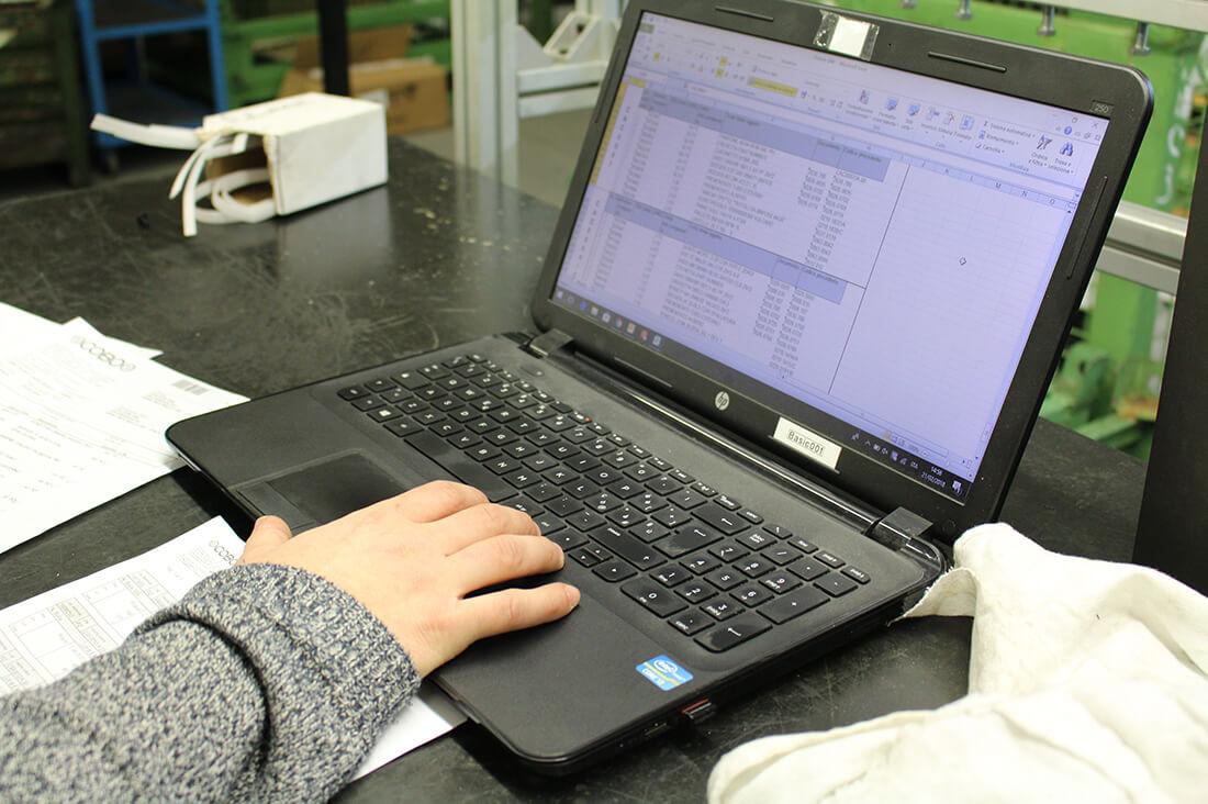 Dettaglio della mano di un impiegato mentre digita sulla tastiera di un computer, seduto alla scrivania.