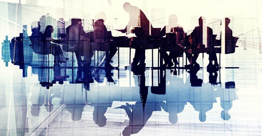 Foto di una vetrata con riflesse le sagome di un gruppo di lavoro seduto a un tavolo in riunione.