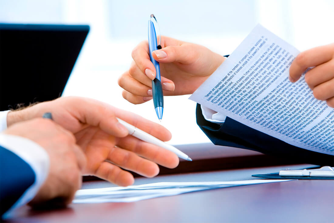 Dettagli delle mani di due impiegati che consultano dei documenti in ufficio.