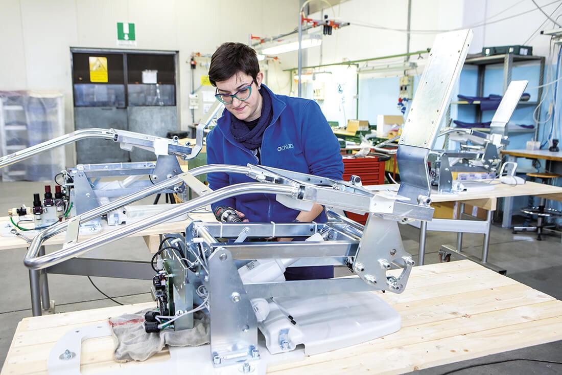 Foto di un'operaia di Calzoni Assemblaggi che assembla un macchinario estetico-medicale.