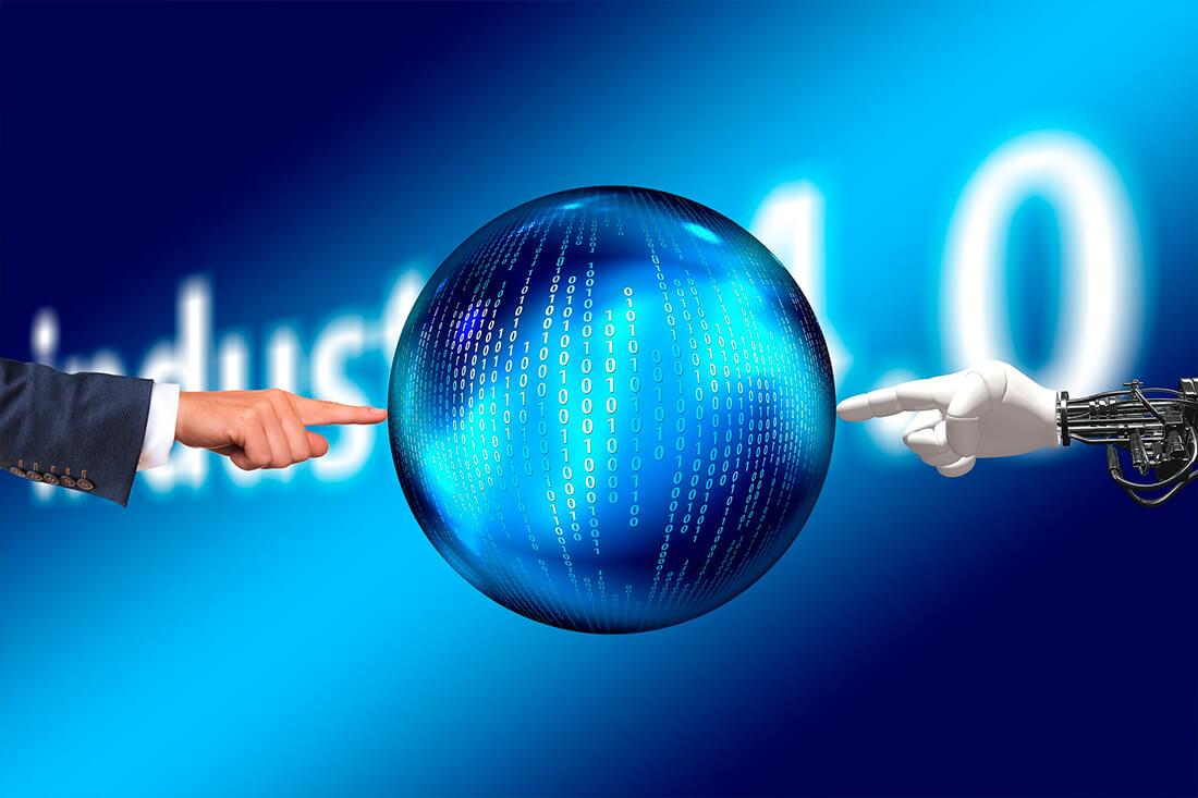 Immagine di una mano umana e di una mano robot che indicano ai lati una sfera digitale con all'interno codici binari.