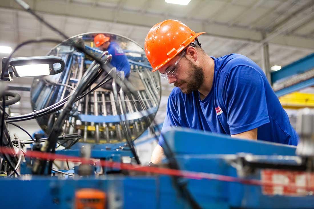 Operaio con casco a lavoro in fabbrica